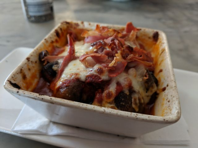 Mushrooms baked in tomato and cheese with prosciutto