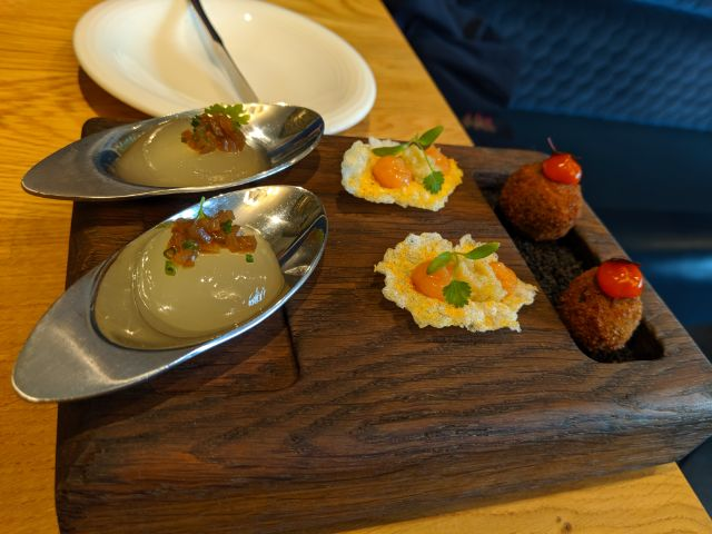 Beef bonbon with sriracha, curried rice cracker with guava and lime, and bloody Mary yolk